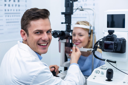 slit: Portrait of smiling optometrist examining female patient on slit lamp in ophthalmology clinic