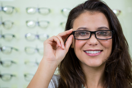 wearing spectacles: Portrait of smiling female customer wearing spectacles in optical store Stock Photo