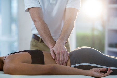 Male physiotherapist giving back massage to female patient in clinic Stock Photo