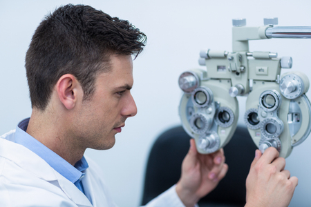 ophthalmology: Attentive optometrist adjusting phoropter in ophthalmology clinic Stock Photo