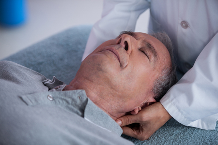 neck massage: Senior man receiving neck massage from physiotherapist in clinic Stock Photo