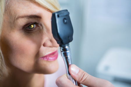 optometrist: Optometrist examining female patient through ophthalmoscope in ophthalmology clinic