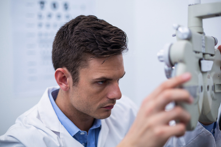 ophthalmology: Attentive optometrist looking through phoropter in ophthalmology clinic