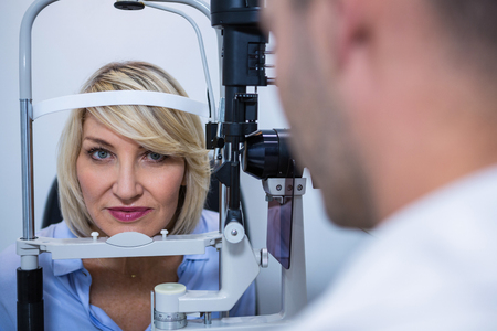 slit: Optometrist examining female patient on slit lamp in ophthalmology clinic