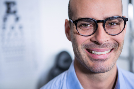 Portrait of smiling optometrist wearing spectacles in ophthalmology clinic