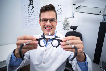 optometrist: Portrait of smiling optometrist holding messbrille in ophthalmology clinic