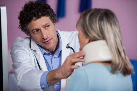 senior man on a neck pain: Physiotherapist examining a female patients neck in clinic Stock Photo