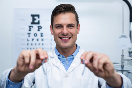 ophthalmology: Smiling optometrist holding spectacles in ophthalmology clinic Stock Photo