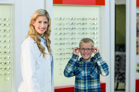 Portrait of female optometrist and young patient in ophthalmology clinic Stock Photo