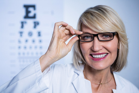 wearing spectacles: Portrait of smiling optometrist wearing spectacles in ophthalmology clinic