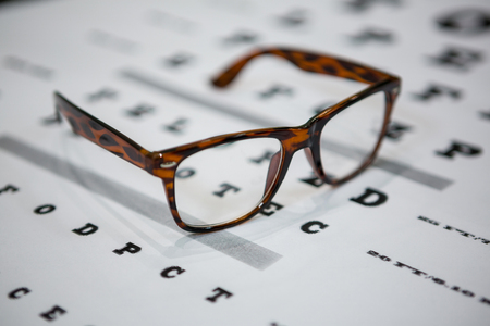 eye chart: Close-up of spectacles on eye chart in ophthalmology clinic Stock Photo