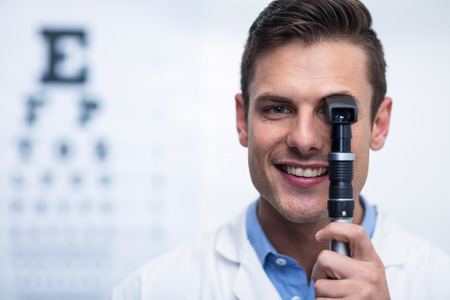 Close-up of smiling optometrist looking through ophthalmoscope in ophthalmology clinic Banque d'images
