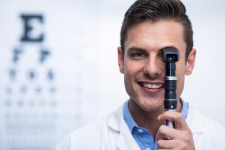 Primer plano de la sonrisa optometrista mirando a través de oftalmoscopio en la clínica de oftalmología