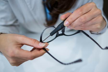 Mitte Abschnitt des Optikers Reparatur Brille mit Werkzeug in der optischen Speicher Standard-Bild