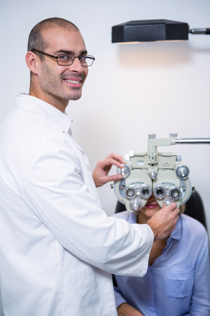 test equipment: Smiling optometrist examining female patient on phoropter in ophthalmology clinic