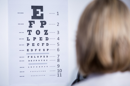 eye chart: optometrist looking at eye chart in ophthalmology clinic Stock Photo