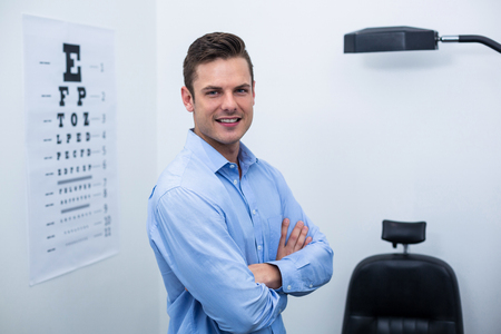 surgical light: Portrait of handsome optometrist standing with arms crossed in ophthalmology clinic Stock Photo