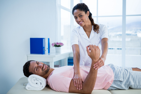 recuperation: Physiotherapist giving hand massage to a patient in clinic