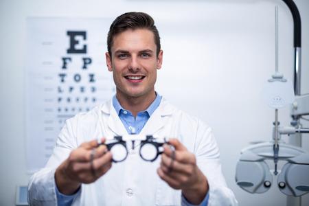 眼科クリニックで messbrille を保持している笑顔の検眼医の肖像画