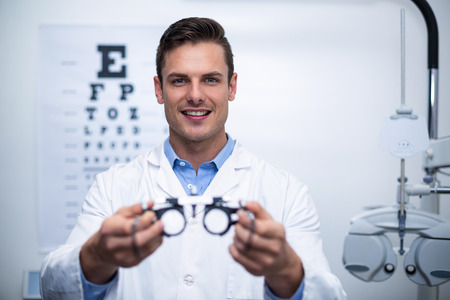 Portrait de sourire optométriste tenant messbrille en ophtalmologie clinique
