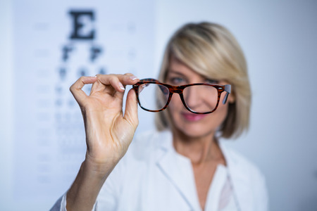 ophthalmology: Female optometrist holding spectacles in ophthalmology clinic