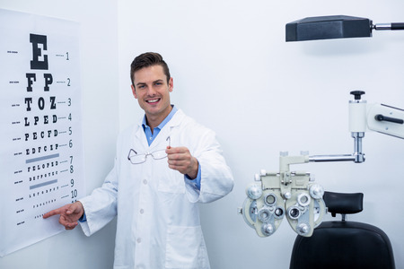 eye chart: Handsome optometrist pointing at eye chart in ophthalmology clinic