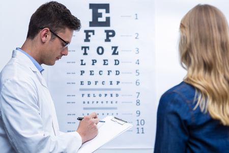 optometrist: Optometrist writing on clipboard in ophthalmology clinic Stock Photo