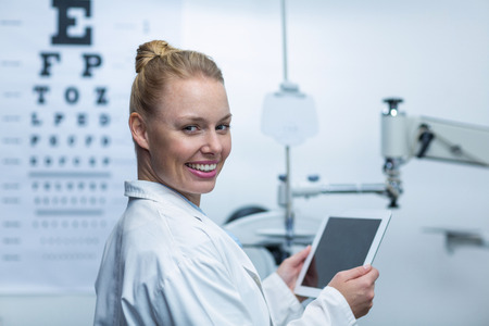 Portrait of smiling optometrist using digital tablet in ophthalmology clinic