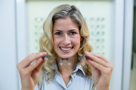 trying: Portrait of smiling female customer trying spectacles in optical store Stock Photo