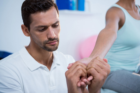 recuperation: Physiotherapist giving hand massage to a woman in clinic