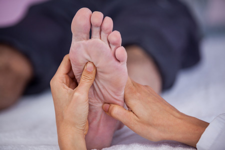 Senior man receiving foot massage from physiotherapist in clinic Stock Photo