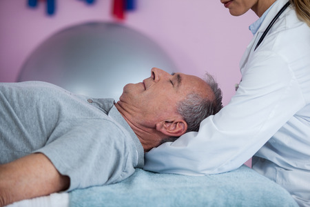 senior man on a neck pain: Senior man receiving neck massage from physiotherapist in clinic Stock Photo