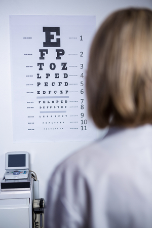 ophthalmology: optometrist looking at eye chart in ophthalmology clinic Stock Photo
