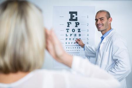 optician: Male optometrist taking eye test of female patient in ophthalmology clinic