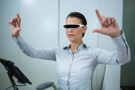 testing vision: Woman using virtual video glasses in optical store