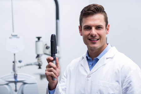 optometrist: Smiling optometrist holding ophthalmoscope in ophthalmology clinic