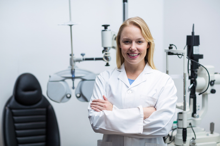 ophthalmology: Portrait of female optometrist standing with arms crossed in ophthalmology clinic