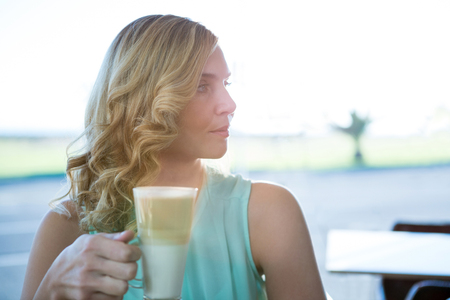 Beautiful woman holding a glass of coffee and looking sideways in the coffee shop