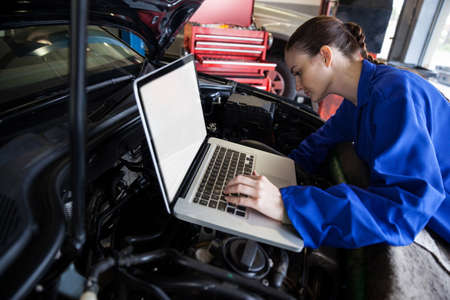 servicing: Female mechanic using a digital tablet while servicing car engine at the repair garage LANG_EVOIMAGES