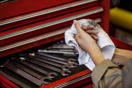 wiping: Mechanic wiping her hand with handkerchief at a repair garage