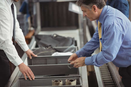 security check: Man putting watch into tray for security check at airport