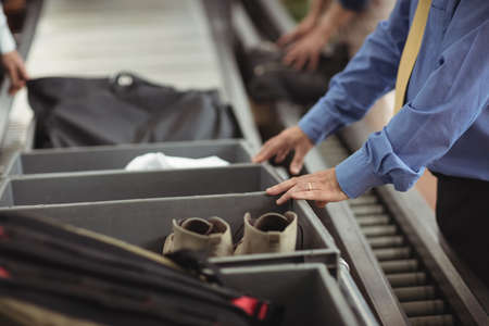 security check: Man putting shoes into tray for security check at airport