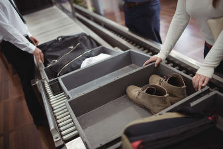 security check: Woman putting shoes into tray for security check at airport