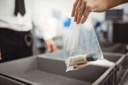 security check: Passenger putting plastic bag into tray for security check at airport