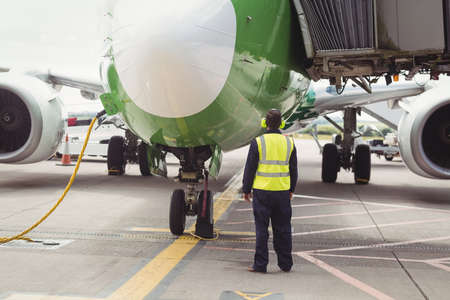 moveable: Rear view of airport ground crew worker directing airplane on runway