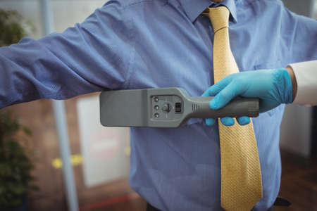 hand held: Airport security officer using a hand held metal detector to check a passenger in airport