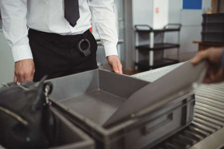 security check: Man putting laptop into tray for airport security check in airport