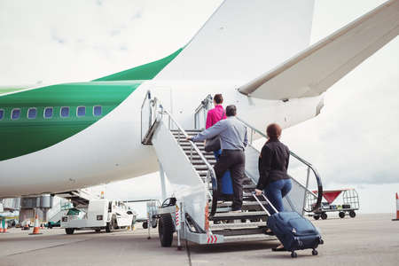 moveable: Passengers climbing on the stairs and entering into the airplane at airport