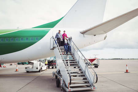 moveable: Passengers exit airplane down stairs at airport