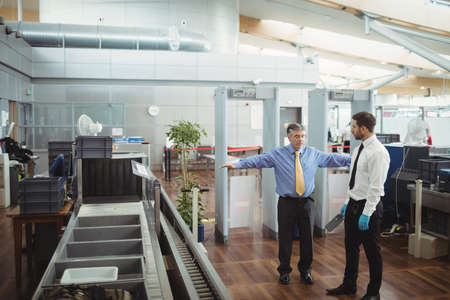 airport security: Airport security officer using a hand held metal detector to check a passenger in airport
